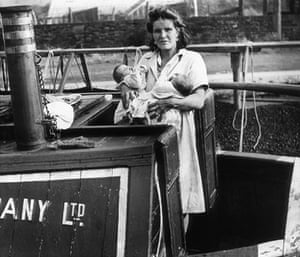 Longden's Canals: A woman stands on a canal boat holding two babies