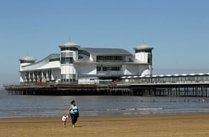 Grand Pier: People walk on the beach in front of the rebuilt Grand Pier