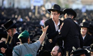 An Israeli border police officer gestures towards ultra-Orthodox Jews during a rally in Jerusalem
