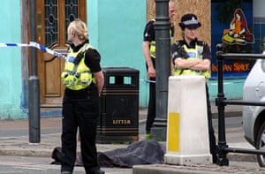 Cumbria shootings: Police stand next to the body of Darren Rewcastle on Duke Street, Whitehaven. Rewcastle, a fellow taxi driver, was Bird's first victim
