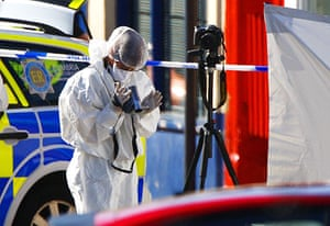 Cumbria shootings: A police forensics team member records evidence at a murder scene