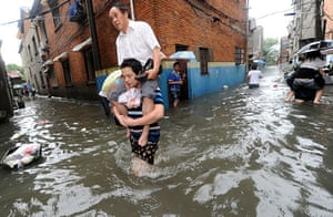 Chian flooding: A young man carries an elder person through flooded street, China