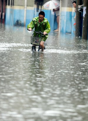 Chian flooding: A person rides his bike in the flood waters, China