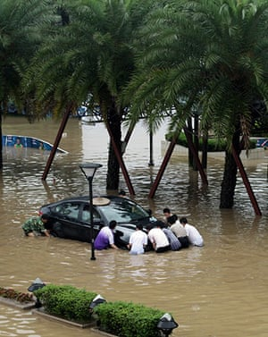 Chian flooding: Chinese residents gather help remove a car as flood waters rise in Guilin