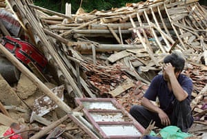 Chian flooding: A resident looks on as he squats in the debris in Taolin village, China