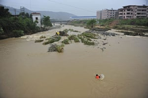 Chian flooding: A rescuer swims to a bus submerged by the flash floods in Nanping