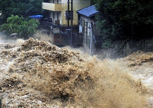 Chian flooding: Flood water roars past houses in the Xiqin township