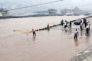 China flooding 2: A man on a submerged road throws a net to fish in the Yangtze River