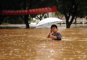 China flooding 2: A man wades through the waterlogged street in Yujiang county