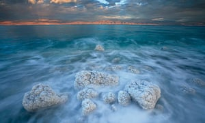 Boulders spiky with salt crystals edge the Dead Sea