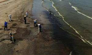 Workers clean up oil on a beach in Grand isle, Louisiana