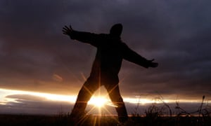 A pagan reveller welcomes in the new sun during an early morning winter solstice celebration