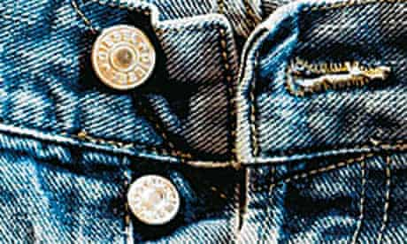 Button fly of an old faded pair of denim jeans