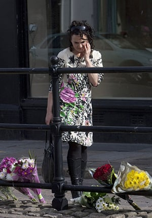 Cumbria shootings: A woman looks at flowers laid in tribute to the victims