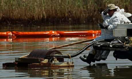Contract workers from BP  use skimmers to clean oil from a marsh in Louisiana.