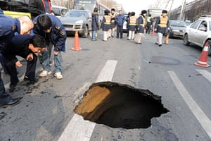 Sinkholes: 2010, Beijing, China: Workers inspect a sinkhole