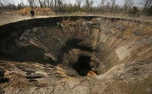 Sinkholes: 2008, Picher, US: John Sparkman is dwarfed as he looks into a sinkhole