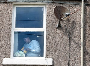 Cumbria shootings: Photographs are removed from a cupboard inside Derrick Bird's house