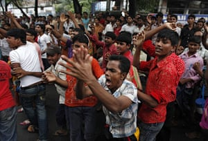 Dhaka protests: Garment workers shout slogans as they block a street in Dhaka