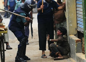 Dhaka protests: A Bangladeshi policeman hits a child with a baton during clashes