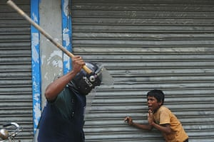 Dhaka protests: A Bangladeshi policeman threatens a child with a baton during clashes