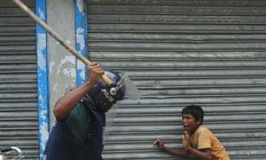 A Bangladeshi policeman threatens a child