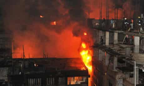 Firefighters and bystanders try to extinguish a large fire in Dhaka, Bangladesh