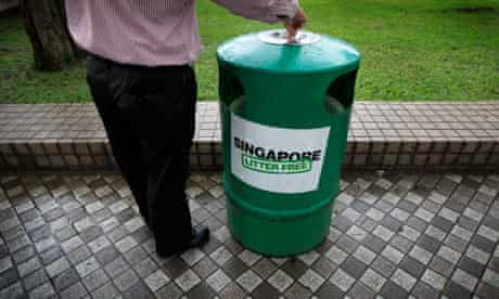 A man stubs out his cigarette on a bin bearing a 'Singapore Litter Free' sticker