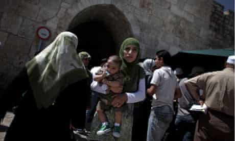 A Palestinian woman walks with her child out of Herod's Gate in the Old City.