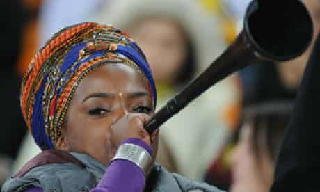 A supporter blows a vuvuzela prior to th