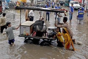 24 hours in pictures: Lahore, Pakistan: A vendor pushes his cart through a flooded street