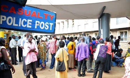 People gather outside the Mulago Hospital casualty section, following blasts in Kampala