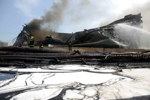 Dalian oil fire in China: Chinese firefighters rest after they ext
