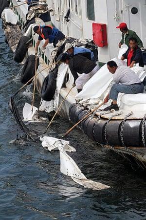 Dalian Oil Spill: Workers on a boat collect crude oil in the sea near Dalian