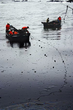Dalian Oil Spill: Chinese firefighters are seen on boats amongst the an oil spill