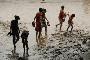 China floods: People wade through mud at the junction of the flooded Yangtze and Jialin rivers
