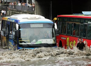 China floods: A man stands in flood waters as two buses pass on a flooded street in Wuhan