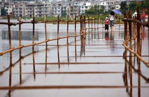China floods: Residents walk across a bridge in the flooded area of Poyang