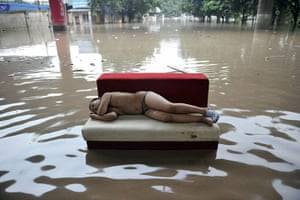 China floods: A child sleeps on a couch on a flooded street in Chongqing municipality