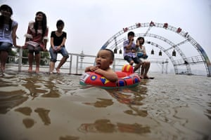 China floods: Residents enjoy the water along a flooded riverbank in Wuhan