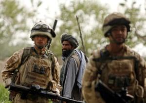 Afghanistan: 27 March 2009: An Afghan man watches British Gurkhas on foot patrol