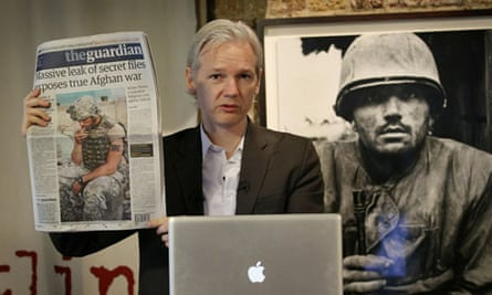 Julian Assange with a copy of the Guardian