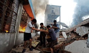 Residents and a firefighter carry a man injured during an explosion at a plastics factory in Nanjing