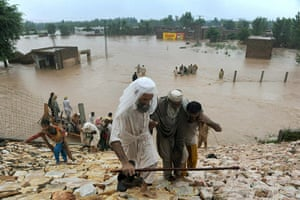 Pakistan floods: Pakistani local residents evacuate in a flood-hit area of Nowshera