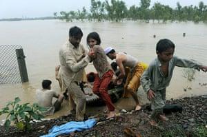Pakistan floods: Pakistani local residents scramble to safety in flood-hit Nowshera