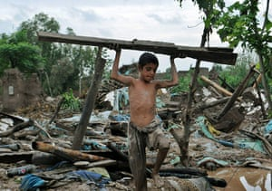 Pakistan floods: Boy removes wood from his collapsed house in the flood-hit area of Nowshera