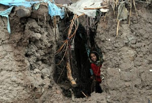Pakistan floods: A girl looks out from her damaged house in the flood-hit area of Nowshera