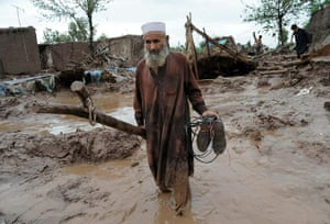 Pakistan floods: A man carries some of his belongings as he leaves behind his damaged house