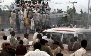 Pakistan floods: Pakistani villagers move away from a flood hit village near Nowshera