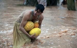 Pakistan floods: A man carries melons as he wades through a flooded street in Peshawar